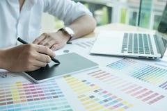 Młody projektant grafik komputerowych pracuje z komputerem i koloru swatch C Zdjęcia Royalty Free