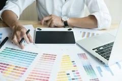 Młody projektant grafik komputerowych pracuje z komputerem i koloru swatch C Obraz Stock