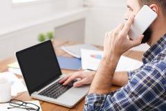 Młody przypadkowy biznesmen pracuje z laptopem i telefonem w biurze, zamyka up Obraz Stock