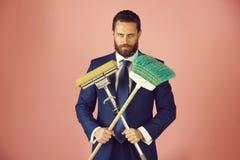 M?ody przystojny biznesmen z cleaning miot?? na r??owym tle zdjęcia royalty free