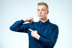 Młody przystojny facet wskazuje przy jego bicepsami Zdjęcia Stock