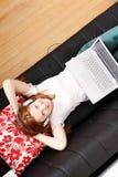 Młody rudzielec dziewczyny surfing na kanapie Zdjęcie Stock