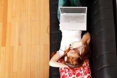 Młody rudzielec dziewczyny surfing na kanapie Zdjęcie Royalty Free