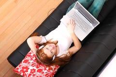 Młody rudzielec dziewczyny surfing na kanapie Obrazy Stock