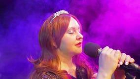 M?ody rudzielec kobiety piosenkarza ?piew na scenie przy mikrofonem w chuchu dym zdjęcie wideo