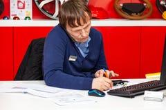 M?ody m?ski administrator opowiada na telefonie przy prac? trzyma telefon jego ucho i robi notatkom na papierze, w tym samym czas zdjęcie royalty free