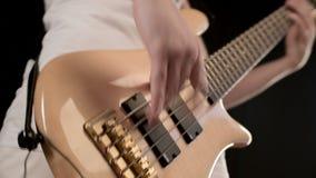 M?ody m?ski muzyk w biel ubraniach z be?ow? basow? gitar? na czarnym tle Basowej gitary gracza ekspresyjna muzyka zdjęcie wideo