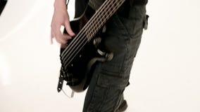 M?ody m?ski muzyk w czerni ubraniach z czarn? basow? gitar? na bia?ym tle Basowej gitary gracza ekspresyjna muzyka zbiory wideo