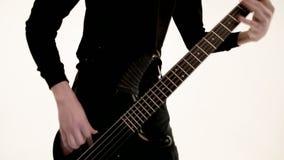 M?ody m?ski muzyk w czerni ubraniach z czarn? basow? gitar? na bia?ym tle Basowej gitary gracza ekspresyjna muzyka zbiory