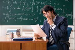 M?ody m?ski nauczyciel matematyki w sali lekcyjnej obrazy royalty free