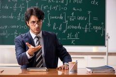 M?ody m?ski nauczyciel matematyki w sali lekcyjnej obraz stock