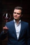 Młody sommelier patrzeje czerwone wino Zdjęcia Stock