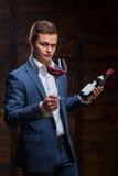 Młody sommelier patrzeje czerwone wino Zdjęcie Royalty Free