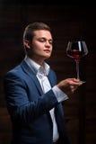 Młody sommelier patrzeje czerwone wino Zdjęcia Royalty Free