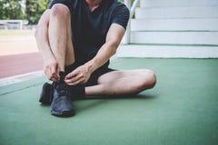 M?ody sprawno?ci fizycznej atlety m??czyzny bieg na droga ?ladzie, ?wiczenie treningu wellness i biegaczu wi??e shoelaces z kopii fotografia royalty free