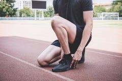 M?ody sprawno?ci fizycznej atlety m??czyzny bieg na droga ?ladzie, ?wiczenie treningu wellness i biegaczu wi??e shoelaces z kopii zdjęcie royalty free