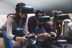 M?ody szcz??liwy trzy przyjaciela bawi? si? gra wideo rzeczywisto?? wirtualn? fotografia stock