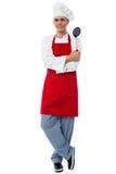 Młody szef kuchni pozuje w stylu z kuchennymi naczyniami Fotografia Stock