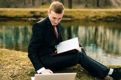 M?ody ucze? studiuje na naturze w parku blisko jeziora facet w czarnym kostiumu czerwonym krawacie i czyta laptop i obraz royalty free