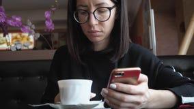 M?ody wonam u?ywa telefon kom?rkowego w wygodnym sklepie z kaw? podczas gdy siedz?cy podczas pracy przerwy, powabny szcz??liwy ?e zbiory