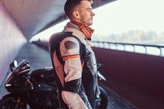 M?ody zadumany rowerzysta stoi blisko jego motobike w spokojnym tunelu zdjęcia stock