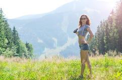 Młodych kobiet spojrzenia przy górami przez lornetek, plenerowy a Zdjęcie Stock