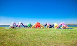 Młodzi ludzie praktyki joga asana na brzeg jeziora Zdjęcia Stock