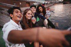 Młodzi ludzie robi selfie na jetty Fotografia Stock