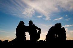 Młodzi ludzie sylwetek przy zmierzchem Fotografia Royalty Free