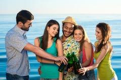 Młodzi ludzie z piwem na tle morze Zdjęcia Royalty Free