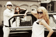 Młodzi modni ludzie przy retro samochodem Obraz Royalty Free