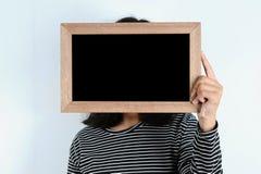 M?os asi?ticas da mulher que guardam o quadro-negro fotografia de stock royalty free