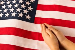 M?os da menina rezando no fundo da bandeira americana O conceito do patriotismo imagens de stock