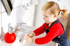 M?os de lavagem da menina pequena bonito da crian?a com sab?o e ?gua no banheiro Crian?a ador?vel que aprende partes do corpo de  fotografia de stock royalty free