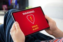 M?os do homem que guardam a tabuleta do computador com alerta de advert?ncia do v?rus fotografia de stock royalty free