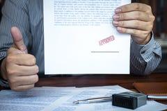 M?os do selo do homem de neg?cios no documento de papel para aprovar o acordo de contrato do investimento empresarial foto de stock