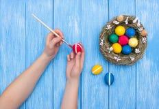 M?os dos ovos da p?scoa da pintura da menina com uma escova e uma pintura em uma tabela azul de madeira em que h? um ninho com ov fotografia de stock royalty free