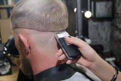 M?quina de corte do cabelo do barbeiro O mestre fornece um corte de cabelo fotos de stock royalty free