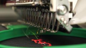 M?quina de coser del robot M?quina de coser autom?tica una m?quina automatizada borda el modelo con los hilos rojos en un negro almacen de video