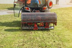 M?quina de Operating Soil Aeration del jardinero en c?sped de la hierba foto de archivo