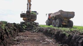 A m?quina escavadora est? carregando um caminh?o com a terra no terreno de constru??o filme