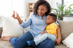 M?re africaine avec le fils de b?b? prenant le selfie ? la maison photo stock