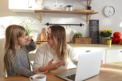 M?re avec la petite fille ? l'aide de l'ordinateur portable dans la cuisine photo stock