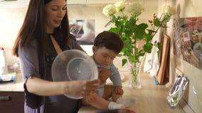 M?re enceinte faisant cuire avec son fils de b?b? dans la cuisine et ayant l'amusement - bleu de port d'appartenance ethnique de  banque de vidéos