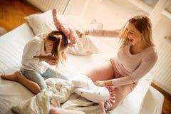 M?re et fille ayant le combat d'oreiller dans le lit photos stock