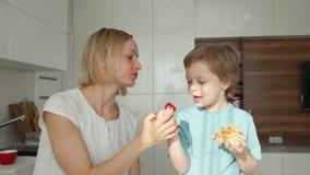 M?re et fils mangeant des fraises ? la cuisine Concept de la famille heureux banque de vidéos