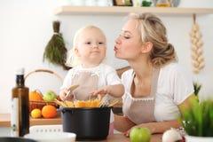 M?re heureuse et petite fille faisant cuire dans la cuisine Temps tout de d?pense ensemble, concept d'amusement de famille images stock