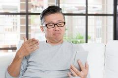 Mûrissez l'homme asiatique malheureux tout en à l'aide du smartphone Photos libres de droits