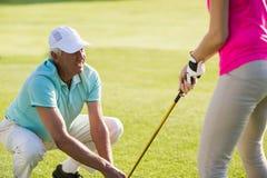 Mûrissez l'homme de golfeur se tapissant tout en enseignant la femme Photos libres de droits