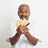 Mûrissez l'homme indien d'affaires occasionnelles tenant beaucoup de cartes de crédit Image stock